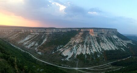 Panorama from the cave town Chufut-Kale on a flat mountain in the sunset light. Crimea, Russia.