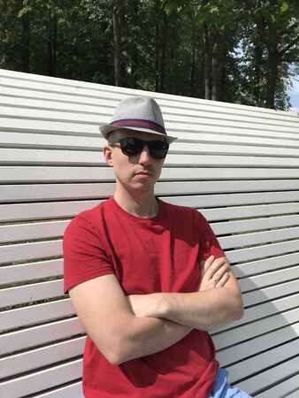 Close up of caucasian young man with a serious face in striped hat, red T-shirt and black sunglasses with arms crossed sits on a white bench in the park and looks into the camera on a sunny day