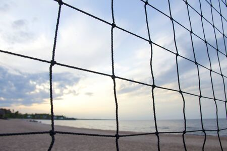 In the foreground closeup of a sports volleyball net. In the background, the blurred sandy beach of the lake, the sunset sky and the houses in front of the forest