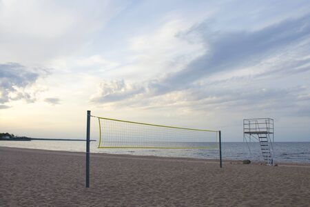 Sports volleyball net on a deserted sandy beach by the lake in the evening against the sunset sky with clouds. Rescue tower nearby