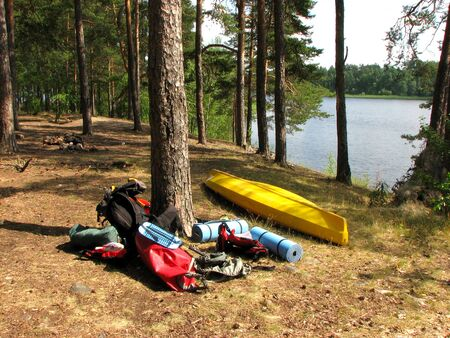 Hiking equipment lies in the sun in the forest by the lake. Kayak, tent, backpack, life jackets, sports mats, barbecue grill