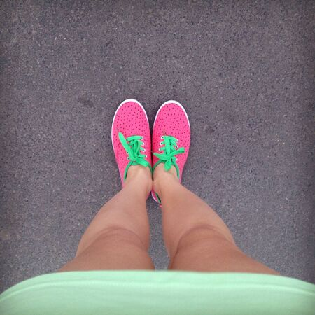 Female legs in bright pink sneakers with green laces on the asphalt. Green dress, sneakers in the form of strawberries. Top view, square photo