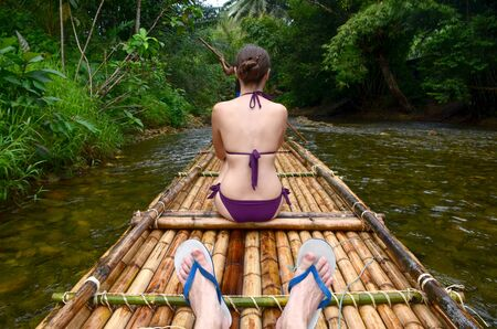 Girl sits on a bamboo raft. Rafting on the river in the jungle. Back view