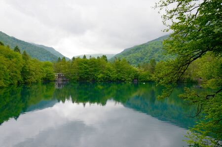 Blue Lake in Kabardino-Balkaria, Caucasus, Russia. Lake surrounded by trees and mountains, symmetrical reflection in the water