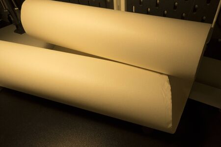 Paper roll in warm dim light with place for text