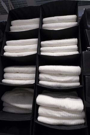 Piles of white terry towels on black hanging shelves. The concept of cleanliness, hygiene, hotel business