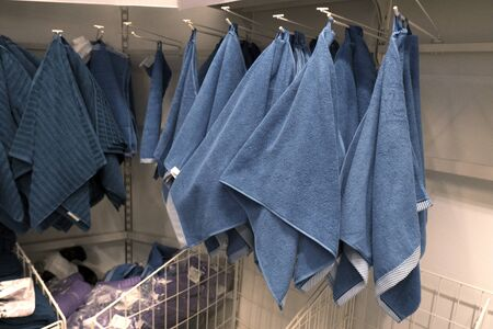 Many blue and purple terry towels hang on hooks in the store. The concept of cleanliness, hygiene, home comfort Фото со стока