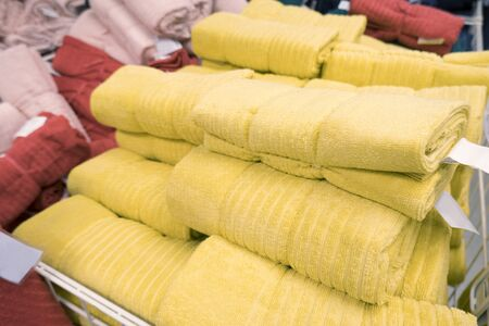 Piles of multi-colored packaged terry towels in a container in a store. The concept of cleanliness, hygiene, home comfort Фото со стока