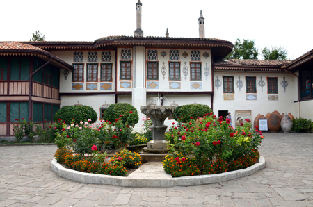 Courtyard of the Khans Palace in Bakhchisarai, Crimea, Russia. Decorative stone fountain surrounded by rose bushes and other flowers
