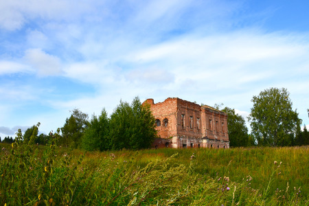 The ruins of an old ruined red brick fortress in thickets of high grass and trees in a meadow against the blue sky with clouds on sunny summer day Editorial