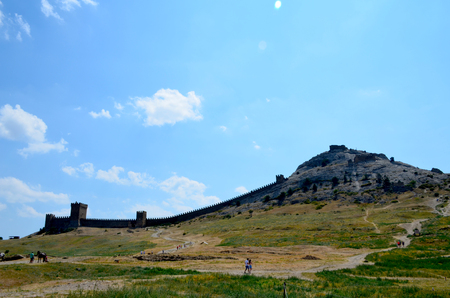 Ruins of the Genoese fortress in Sudak, Crimea, Russia. Tourists walk around the old town on a sunny summer day