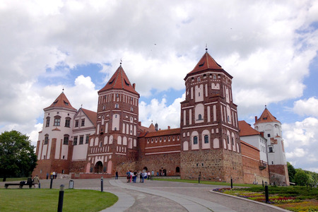 Mir Castle on the background of blue sky with clouds summer day, Belarus. Tourists walk around the castle Editorial