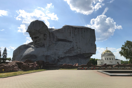 Brest, Belarus - June 10, 2018: Monument Courage and St. Nicholas garrison church in the Brest Fortress, Belarus. Monument on a background of summer blue sky with clouds in the rays of the sun