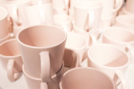 Close up of a heap of many cozy soft pink tea cups in a store