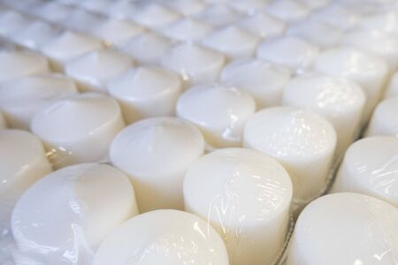 Close up of several rows of white wax candles on a conveyor belt, on a production line in a factory or for sale in a store in transparent packaging, top view, diagonal