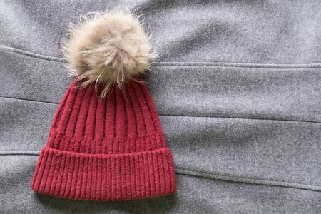 Cozy and warm winter flat lay with copy space. Dark red knitted hat with fur pompom on a gray woolen crumpled background Banco de Imagens