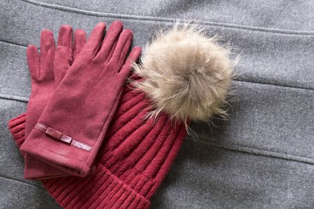 Cozy and warm winter flat lay with copy space. Dark red knitted hat with fur pompom and burgundy gloves on a gray woolen crumpled background