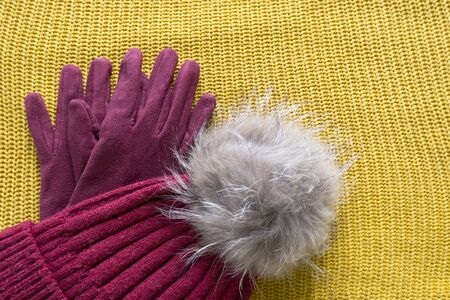 Cozy and warm winter flat lay with copy space. Dark red knitted hat with fur pompom and burgundy gloves on a yellow woolen background