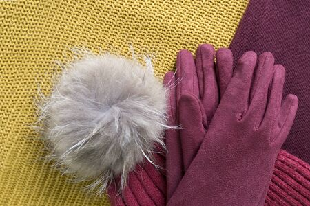Cozy and warm winter flat lay with copy space. Dark red knitted hat with fur pompom and burgundy gloves on a yellow and purple woolen background