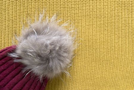 Cozy and warm winter flat lay with copy space. Close up of dark red knitted hat with fur pompom on a yellow woolen background Banco de Imagens