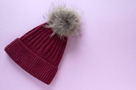 Cozy and warm winter flat lay with copy space. Dark red knitted hat with fur pompom on a pink background