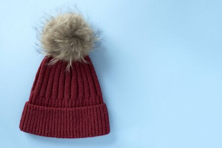 Cozy and warm winter flat lay with copy space. Dark red knitted hat with fur pompom on a light blue background