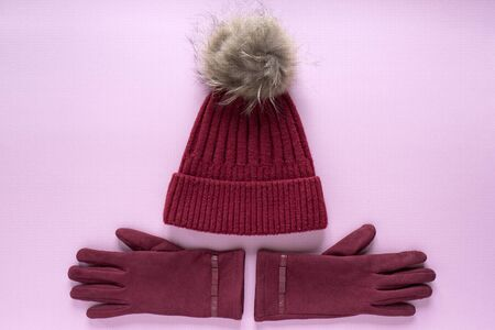 Cozy and warm winter flat lay with copy space. Dark red knitted hat with fur pompom and burgundy gloves on a pink background
