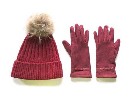 Isolated cozy and warm winter flat lay. Dark red knitted hat with fur pompom and burgundy gloves on a white background