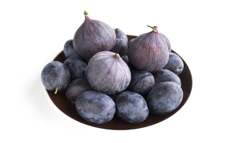 Isolated ripe fruits on a brown plate on a white background. Fruits of blue plum and fig. Side view Banco de Imagens