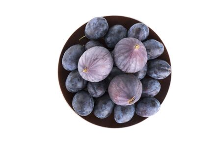 Isolated ripe fruits on a brown plate on a white background. Fruits of blue plum and fig. Top view
