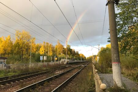 Autumn city landscape. Railroad surrounded by yellow trees in the sunlight. Gloomy sky with rainbow