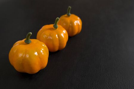 Autumn background of fruits and vegetables: pumpkins on a black background with copy space. Halloween and harvest concept. Banco de Imagens