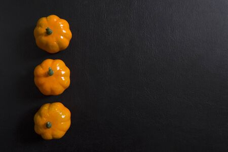 Autumn background of fruits and vegetables: pumpkins on a black background with copy space. Halloween and harvest concept. Stok Fotoğraf