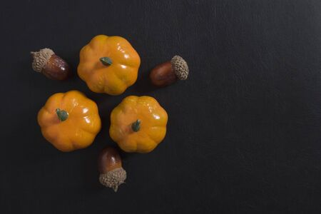 Autumn background of fruits and vegetables: pumpkins and acorns on a black background with copy space. Halloween and harvest concept.