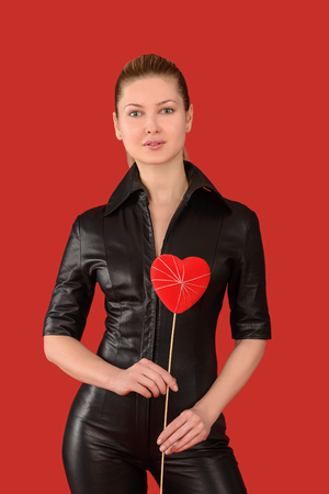 jumpsuit: young girl on a red background on Valentines Day with a red heart in the hands of a black jumpsuit Stock Photo