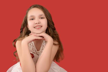 fondo rojo: Adolescente sonriente en traje blanco sobre fondo rojo.