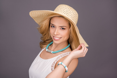 cute lady: young woman on gray background smiling in sun hat with fields. Fashion and beauty. beautiful teenager girl in white dress. makeup and hairstyle. necklace of beads