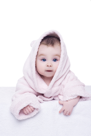 girls bathing: portrait of baby girl on white background. cute little baby girl with big blue eyes in pink bathrobe hood lying on her belly. child is looking into the camera