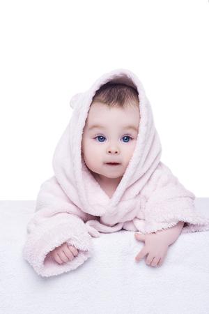 ba�andose: retrato de la ni�a en el fondo blanco. linda ni�a peque�a con grandes ojos azules en la campana bata rosada que miente en su vientre. ni�o est� mirando a la c�mara