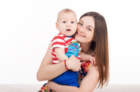 looking into camera: happy mother holding her cute baby. mom and child looking into camera. happy family concept
