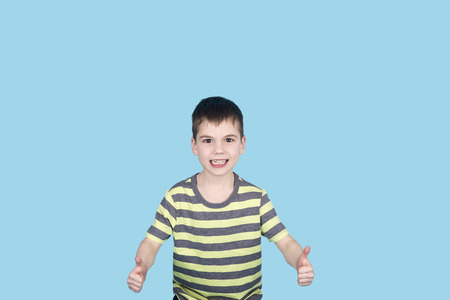 brunnet: teenager boy smiling and looking into camera on blue background, isolated. kid showing thumb up Stock Photo