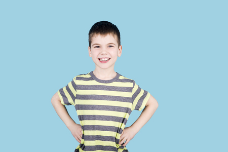 brunnet: teenager boy smiling and looking into camera on blue background, isolated