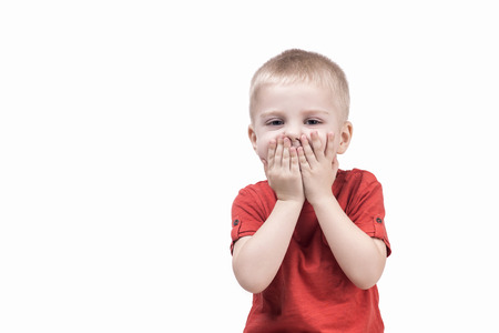 closed mouth: cute child boy surprised by something and closed mouth hands. teenager on white background Stock Photo