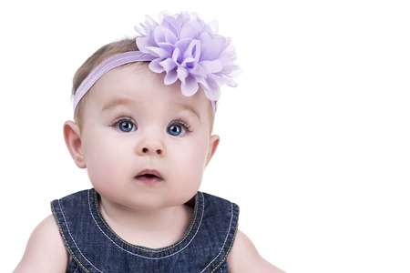 baby isolated: portrait of cute little baby girl with bow flower on her head. kid looks into the camera with admiration. child girl with big blue eyes. happy family concept