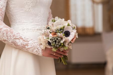 nuptials: bride holding beautiful wedding bouquet in hands