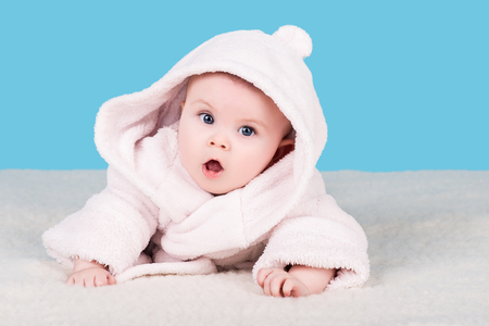 cute baby lying on soft blanket in pink bathrobe with hood and with surprise looks into the camera, isolated on blue