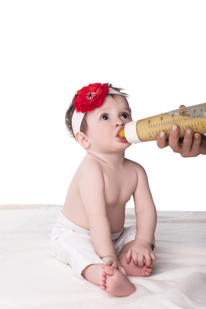 cute baby girl sitting on soft blanket and eating milk from bottle, isolated on white Stock Photo