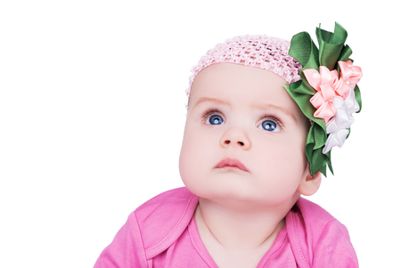 portrait of cute little baby girl with bow flower on her head. child with big blue eyes looks into the camera, isolated on white background Stock Photo