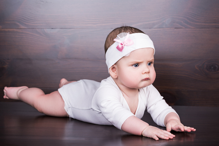 cute serious little baby girl with bow flower on her head. child with big blue eyes lies on his belly on the boards of brown color, over brown wooden background