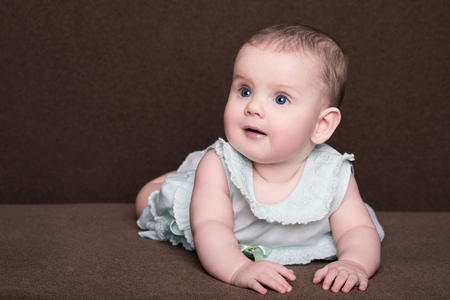 smiling little baby girl in summer dress with big blue eyes lies on his belly over brown background